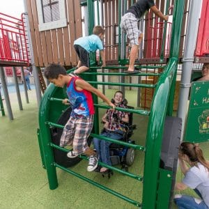 Thumbnail of children climbing on a tractor playground alongside a child in a wheelchair.