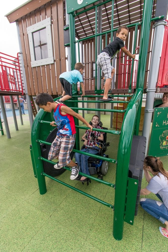 children climbing on a tractor playground alongside a child in a wheelchair.