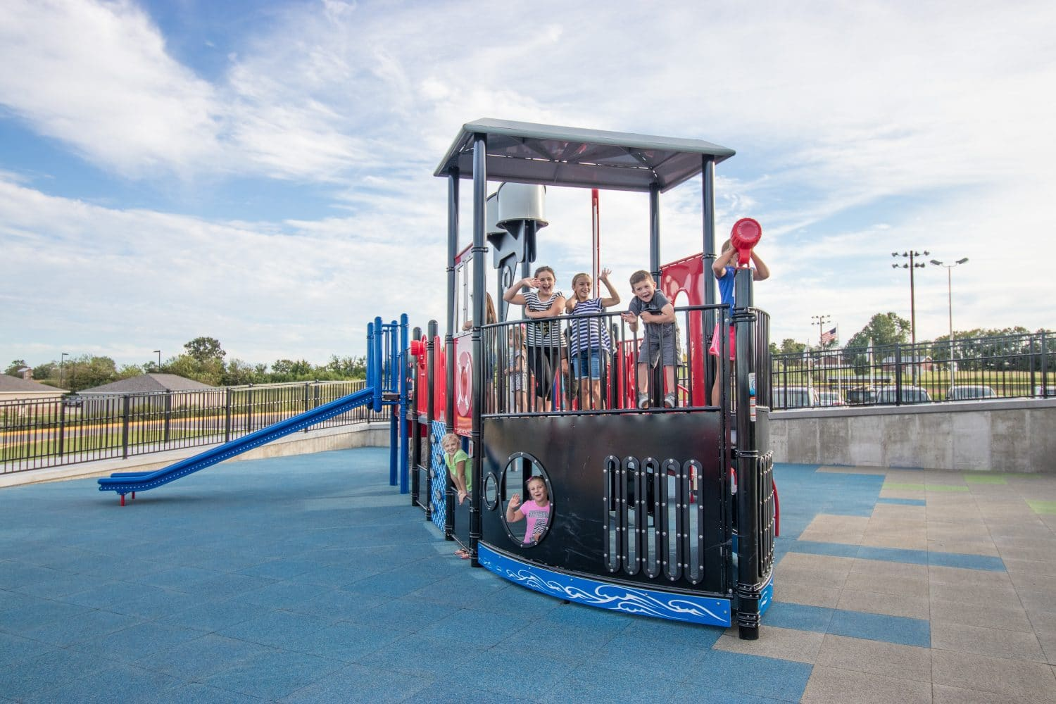 Children playing on a playground that looks like a riverboat.
