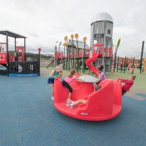 Thumbnail of Children playing on an inclusive spinner.