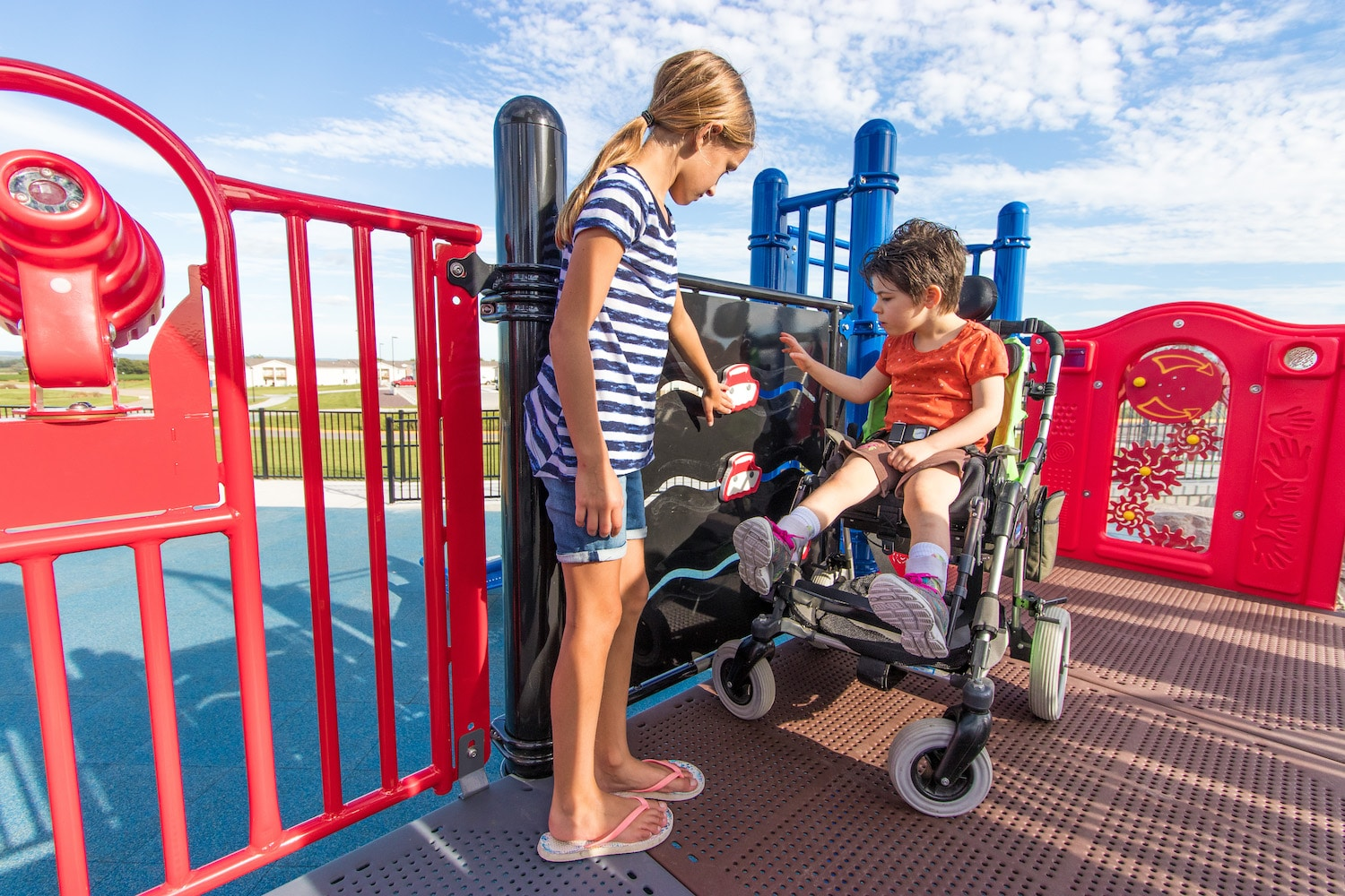 A child in a wheelchair plays alongside an able-bodied child at Braden and Friends Challenger Playground.