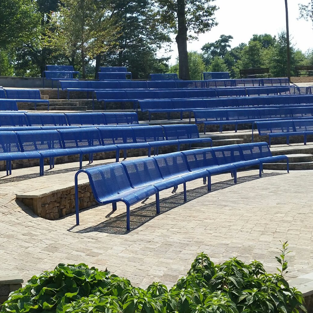 Rows of blue benches in an amphitheater.