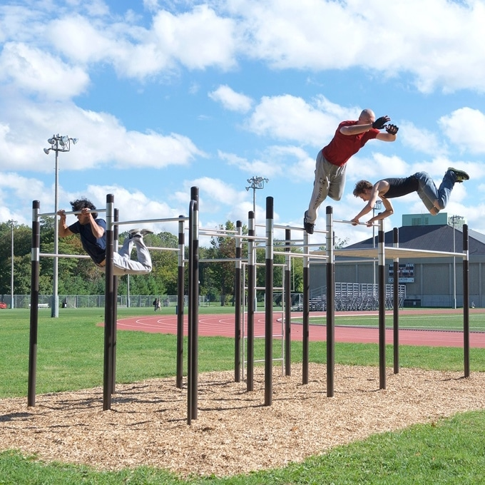 Three people swinging and working out on calisthenics bars.