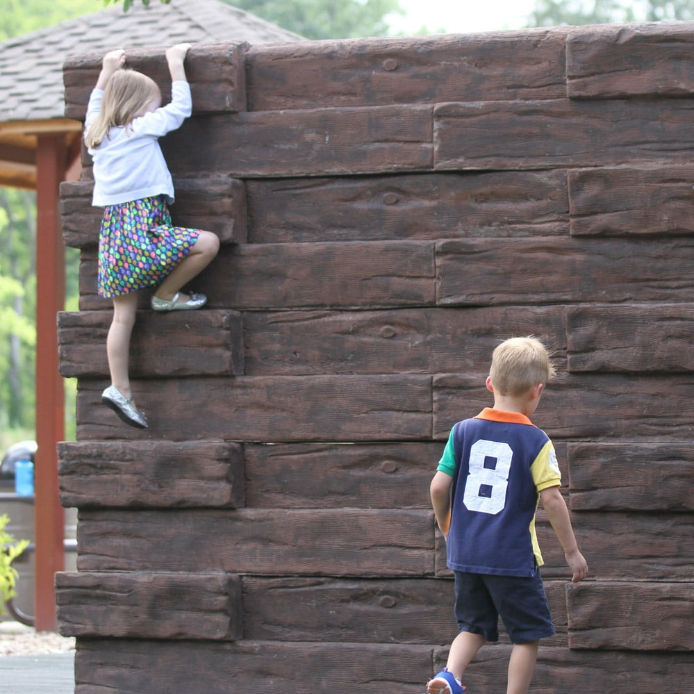 Two kids climbing a wall.