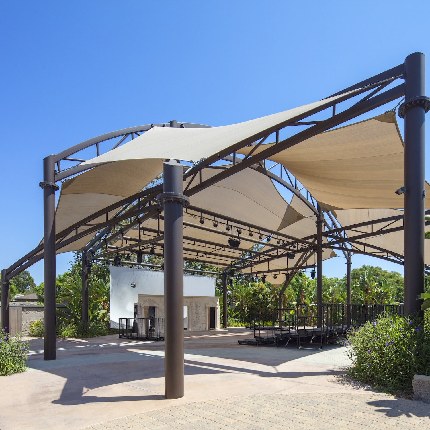 Large tan fabric shade constructed over an outdoor amphitheater.