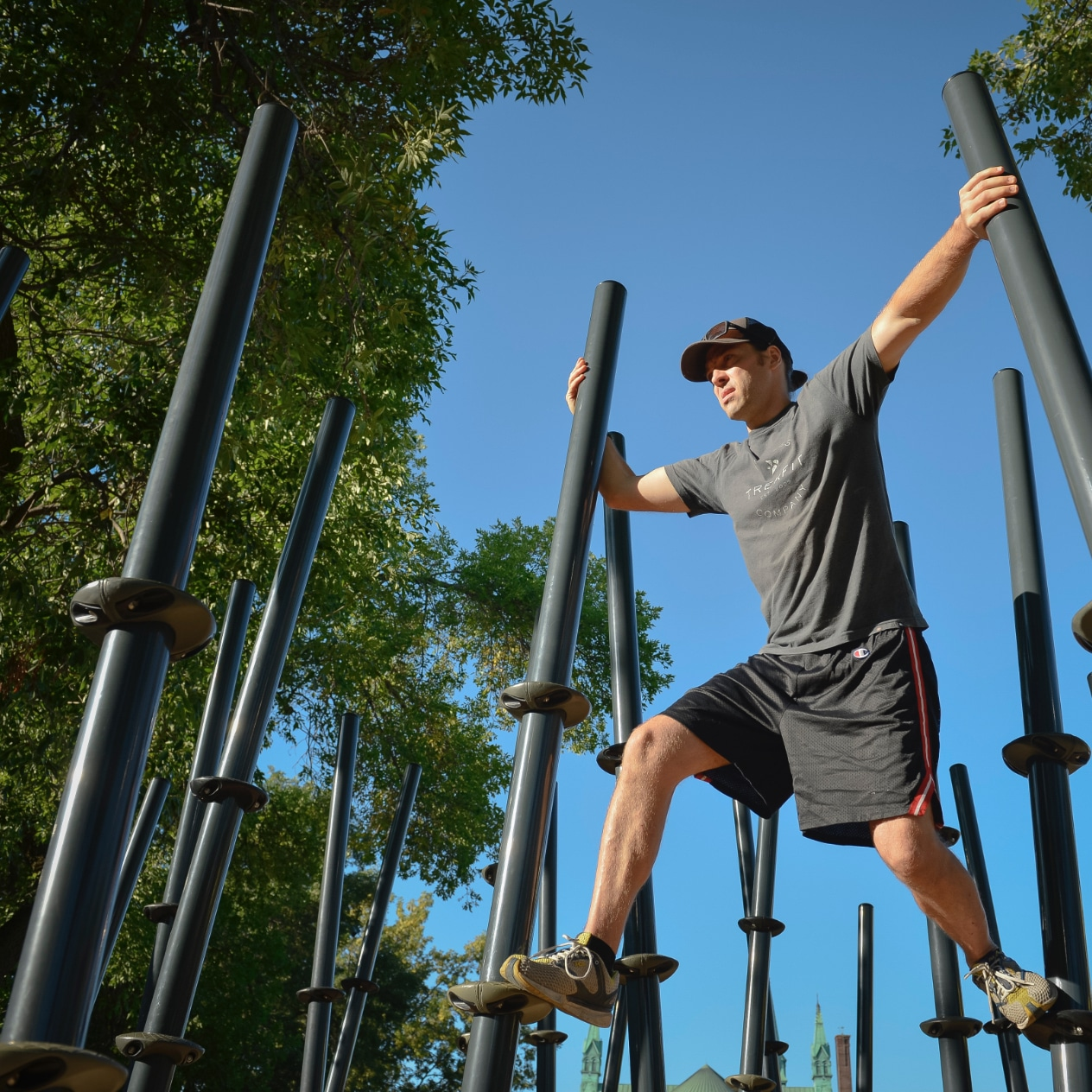 Person climbing through an outdoor obstacle course.