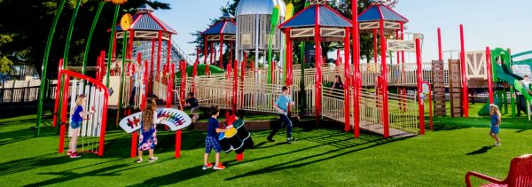 Children playing outdoor musical instruments at a colorful playground.