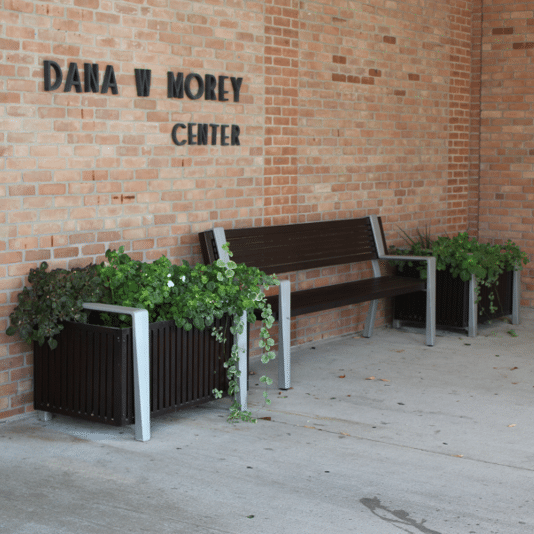 Commercial flower planters and a bench outside a community center.