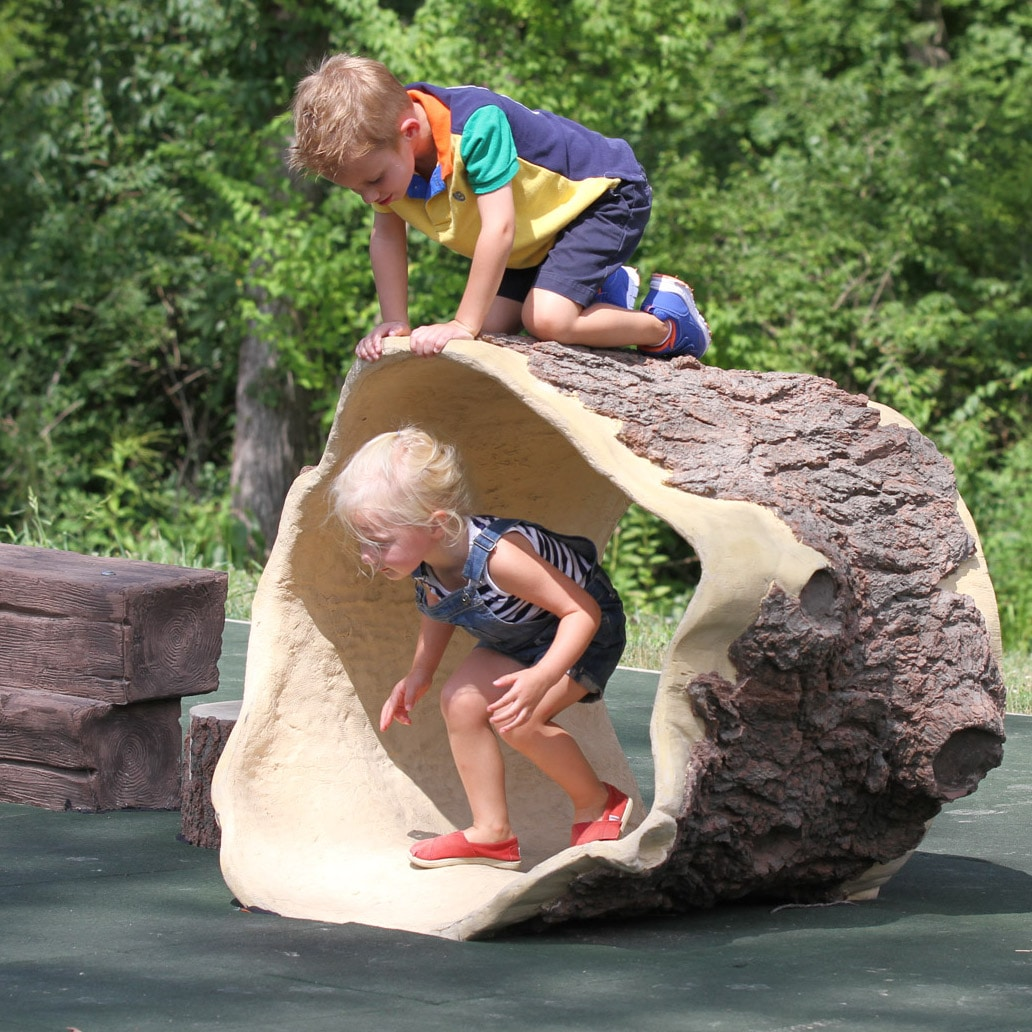 Sculpture of a hollow tree with kids climbing on it.