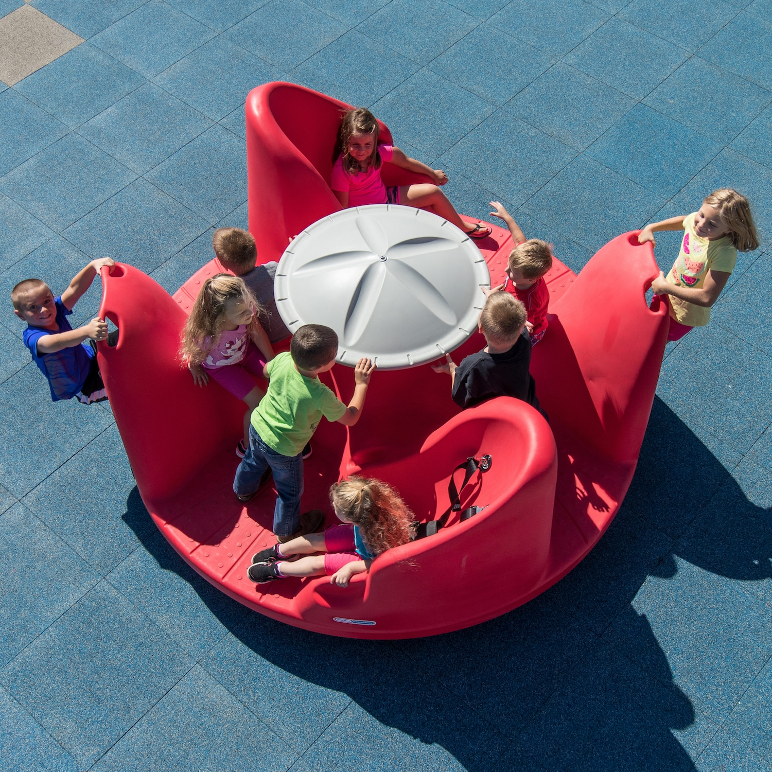 Children laughing and playing on a playground spinner.