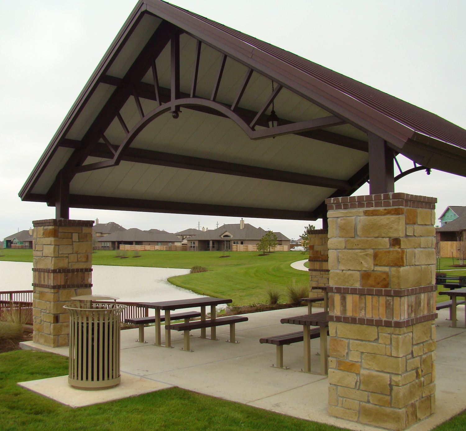 Stone and brown steel shelter with picnic benches near a lake in a neighborhood.