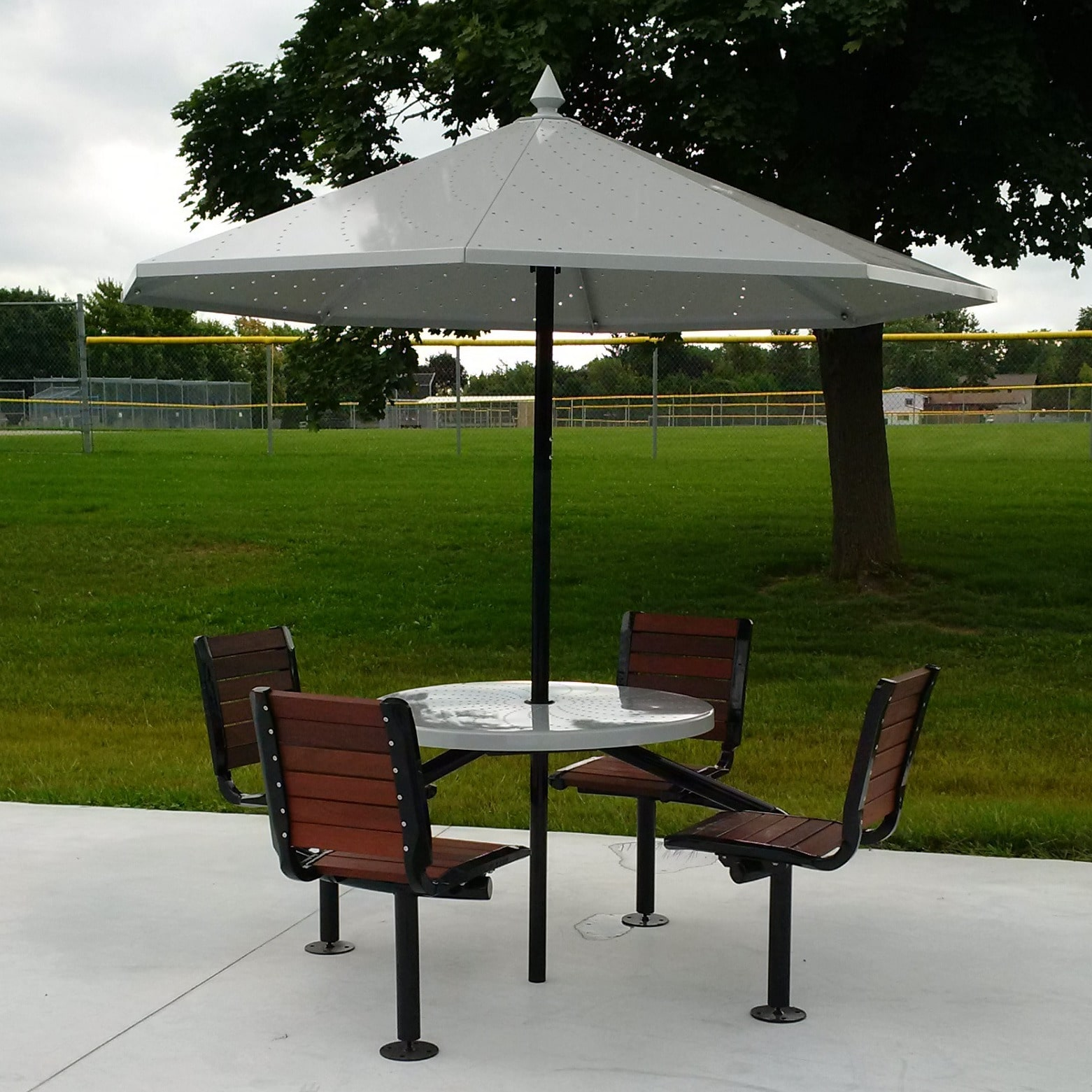 Four wooden chairs connected to an outdoor table with metal umbrella.