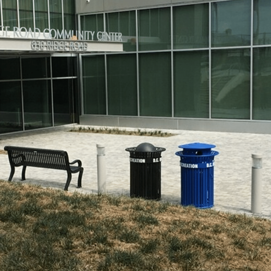 Trash receptacles and a black bench outside a community center