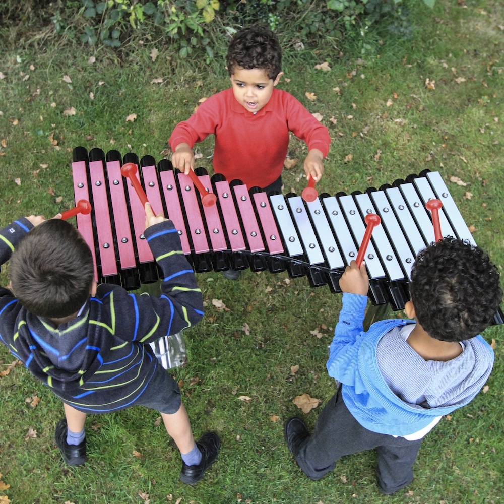 Three children make music playing on The Duo xylophone.