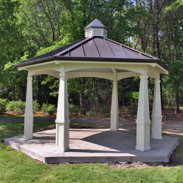 A gazebo with white pillars and gray roof in a park setting.