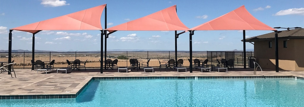 Three salmon colored fabric shades cover the seating area next to a pool.