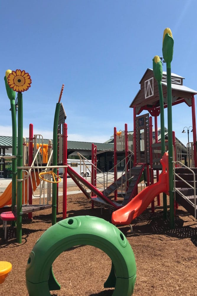 A small red slide on a barnyard themed playground
