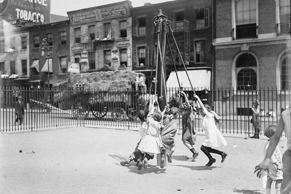 Children hold on to ropes and swing around a maypole in a black and white photo.
