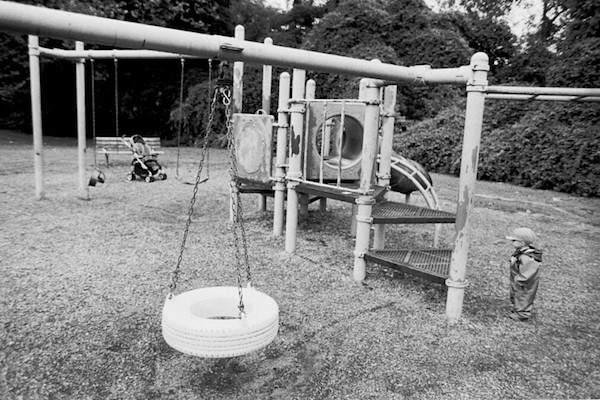 Tire swing on an old playground with a young child ready to play.