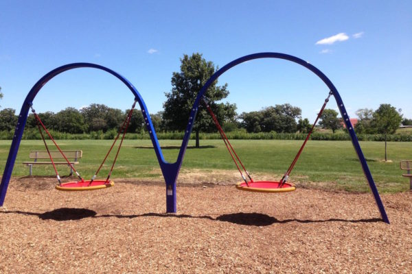 Two saucer swings on a new playground.