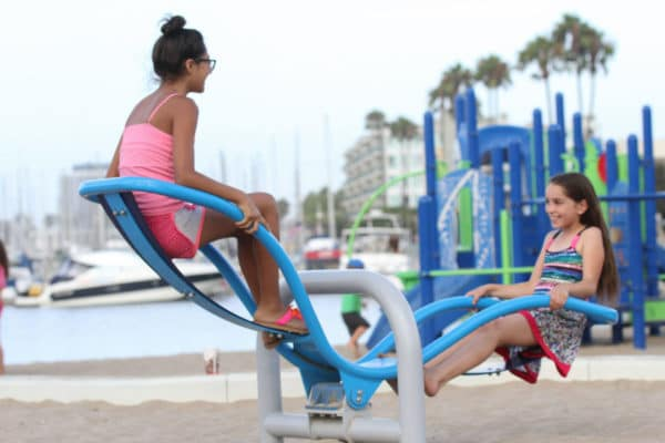 Two girls playing on a modern seesaw.