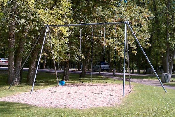 Old swing set with three swings.