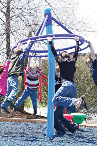 A group of kids swing around a modern maypole by hanging on to the rim.