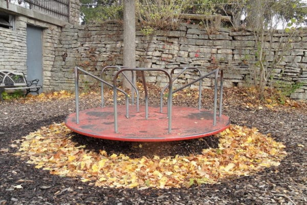 Old metal merry-go-round on a playground.